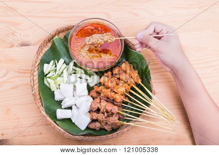 Hand holding satay served on traditional rattan plate with ingredients