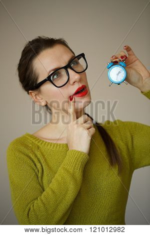 Little Blue Alarm Clock In The Hands Of Pensive Young Woman