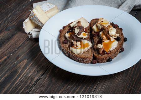 Melted Brie With Honey, Pine Nuts And Walnuts On Dark Bread