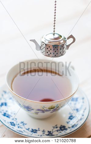 Brewing tea with tea infuser and tea in cup