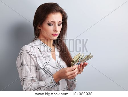 Young Serious Woman Looking And Counting Dollars And Thinking How Little Money She Have Earned And H