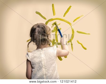 The child draws the sun on the wall