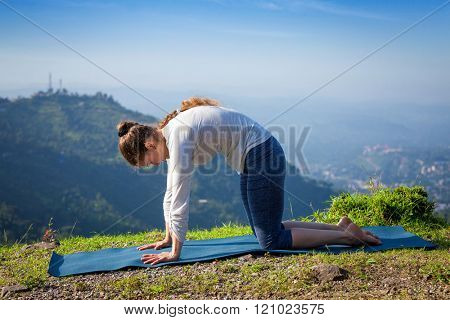 Sporty fit woman practices yoga asana Marjariasana - cat pose outdoors in Himalayas