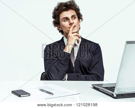 Thoughtful businessman looking up with concentration at office.