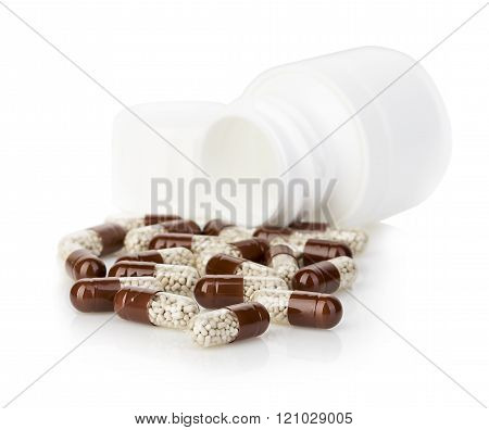 Brown capsules, pills poured out of a white bottle close-up on a white background.