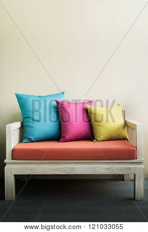 Colorful 3 Pillows On A White Chair