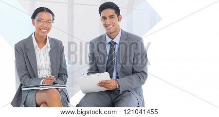Portrait of smiling business people with paperwork against room with large window looking on city