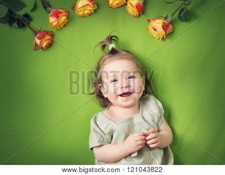 pretty little girl lying on green blanket with yellow roses