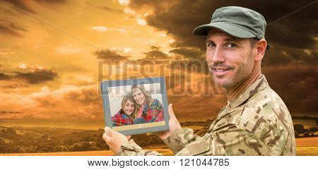 Soldier using tablet pc against country scene
