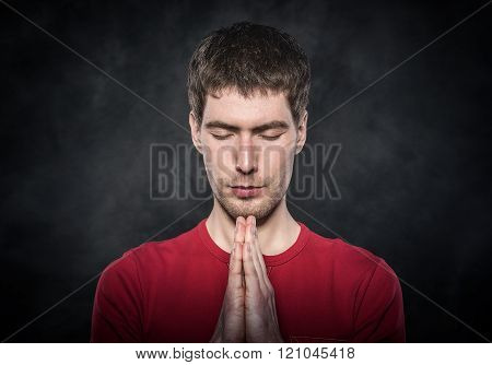 Man praying with hands clasped.