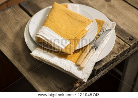 Dinner Plates And Orange Napkins Stack With Knife And Fork