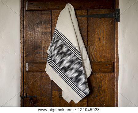 White Towel With Black Herringbone And Stripes Hanging On  Door