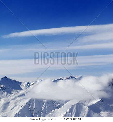 Snow mountains in clouds at sun day