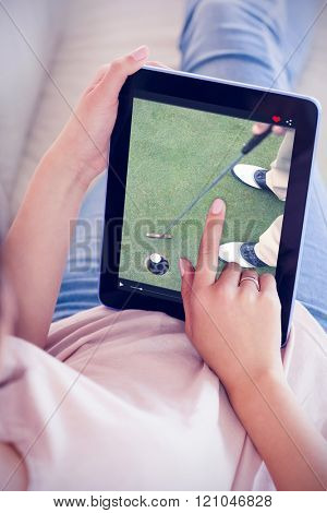 Girl using her tablet on the couch against golfer putting golf ball in the hole