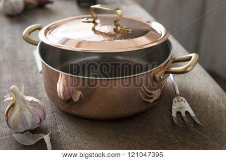 Partially Covered Copper Cooking Pot Between Garlic And Carving Fork