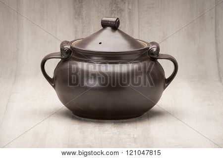 A black tureen or soup bowl or serving bowl with cover on.