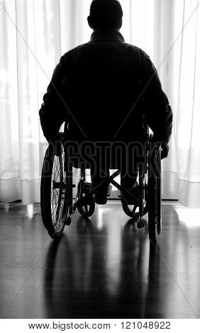 Disabled In A Wheelchair In The Room Near The Window