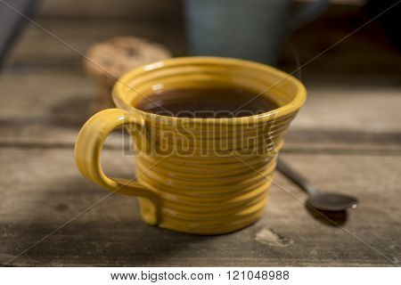 Yellow Cup Containing Coffee Or Tea Beside Spoon