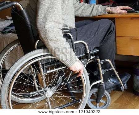 Person Sitting In A Wheelchair At A Desk With Pc