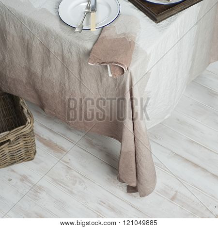 Dinnerware And Napkin On Table Covered In Gradient Brown Linen