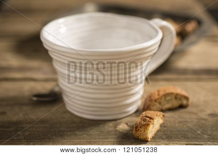 Empty White Teacup Between Spoon And Biscuits