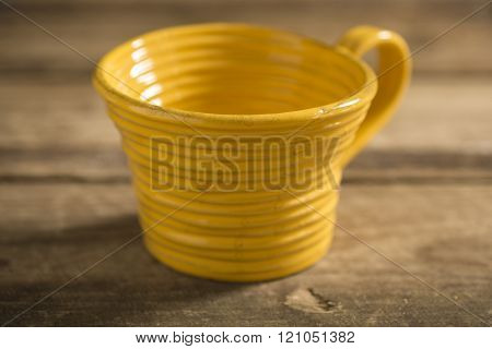 Close Up Of Yellow Teacup On A Wooden Surface