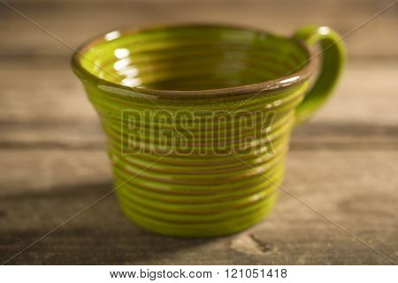 Close Up Of Green Teacup On A Wooden Surface