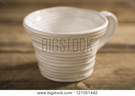 Close Up Of White Teacup On A Wooden Surface
