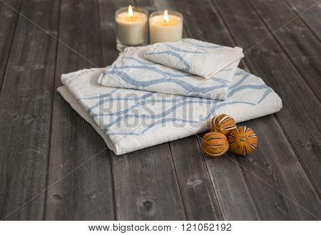 Towels With Blue Concave Lines Alongside Candles And Dried Citrus