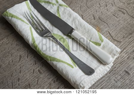 Fork And Knife On White Napkin With Green Concave Lines