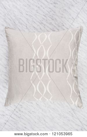Close Up Of Square Gray Throw Pillow Flat On Marble