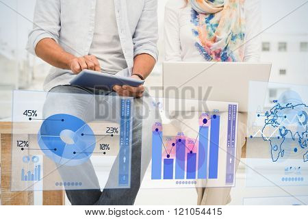 Digitally generated image of pie chart and bar graph against casual designers sitting on wooden desk and using devices