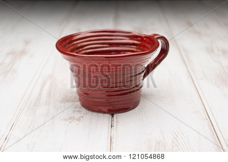 Red Teacup On A White Wooden Panel Surface