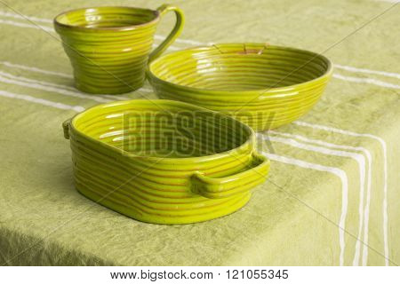 Set Of Green Earthenware On Blue Linen