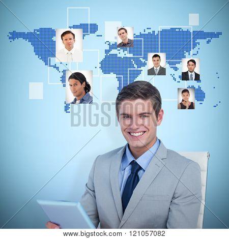 Portrait of smiling businessman using tablet computer against blue background
