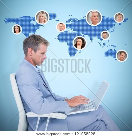 Handsome businessman sitting on a swivel chair and using his laptop against blue background