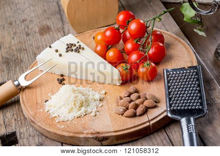 Grated Pecorino Cheese On Wooden Cutting Board With Tomatoes, Selective Focus