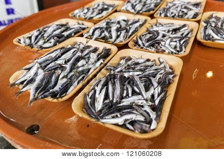 Group of sardines on a colorful bench for sale in fresh seafood market