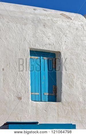 Blue window on medieval white house, island of Mykonos, Greece