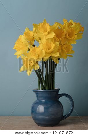 Yellow Spring Daffodils In Blue Jug On Table