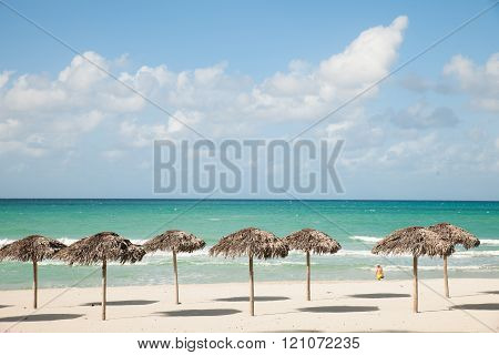 Umbrellas from royal palm leaves, parasole on sandy beach in Varadero on Cuba with turquoise Caribbean sea.