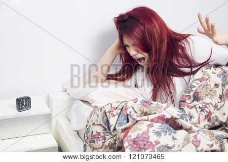 Angry woman waking up, lying on the bed awake