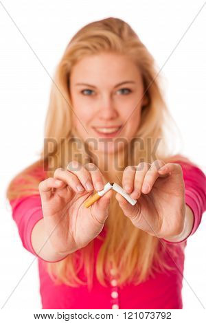 Woman breaking cigarette as a gesture of quitting smoking, breaking unhealhy nicotin adiction.