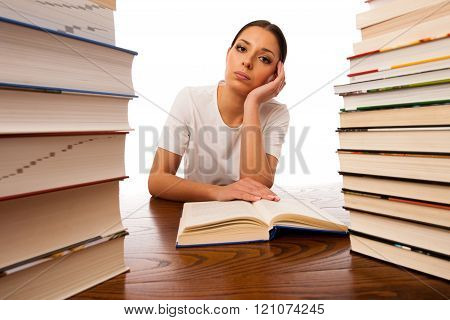 Sick And Tired Woman Reading Behind The Table Between Two Pile Of Books.