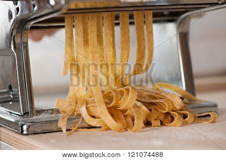 Making noodles with pasta machine from homemade spelt dough.