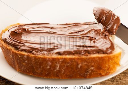 Slice of bread with sweet chocolate nougat spread on wooden background.