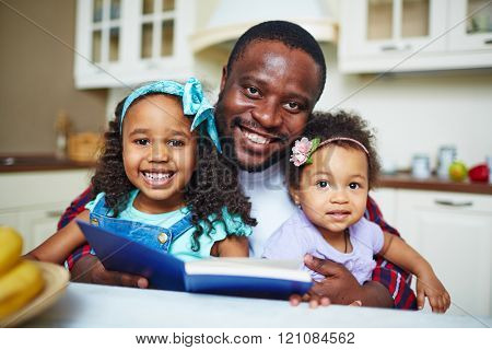 Smiling young father reading a book for his girls