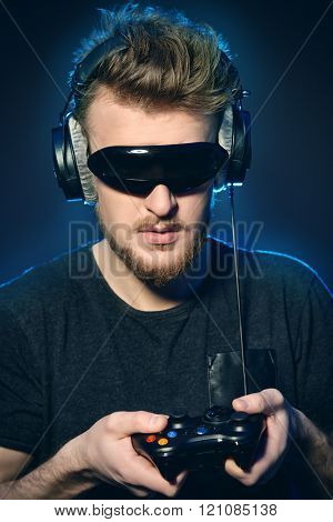 Passionate gamer with controller, headphones and 3d glasses over dark background.