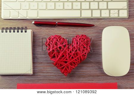 Computer peripherals with red wicker heart, pen and notebook on wooden table