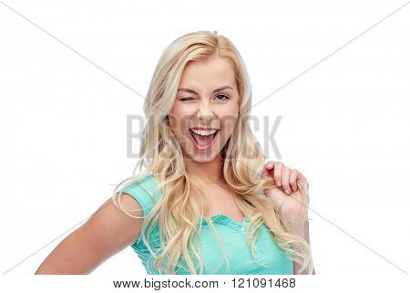 emotions, expressions, hairstyle and people concept - smiling young woman or teenage girl holding her strand of hair and winking